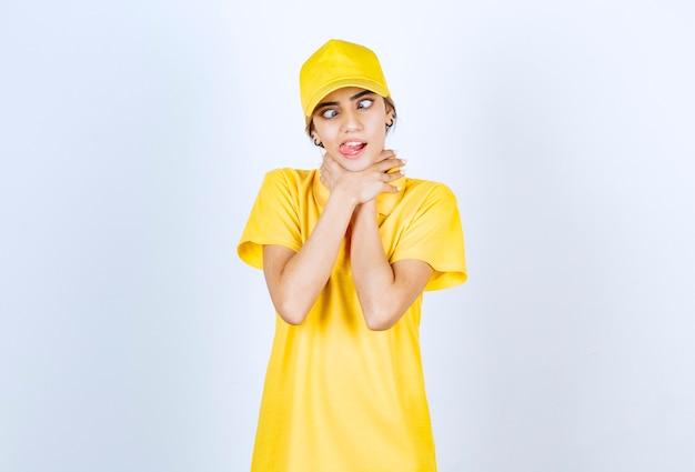 Lieferfrau in gelber uniform steht und erwürgt sich