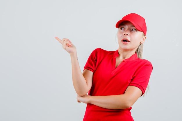 Lieferfrau in rotem t-shirt und mütze zeigt weg und sieht erstaunt aus