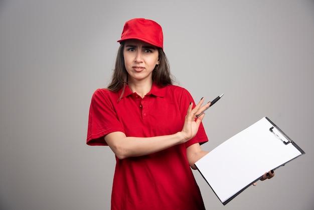 Lieferfrau in roter uniform bleibt von der zwischenablage fern.
