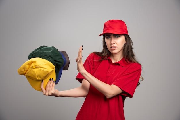 Lieferfrau in roter uniform, die von bunten kappen fern bleibt.