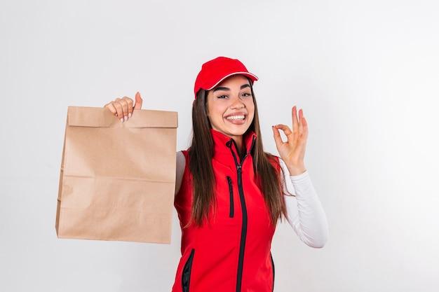 Lieferfrau in roter uniform halten bastelpapierpaket mit essen