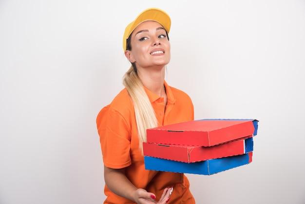 Lieferfrau mit gelbem hut, der pizzaschachteln auf weißem raum hält