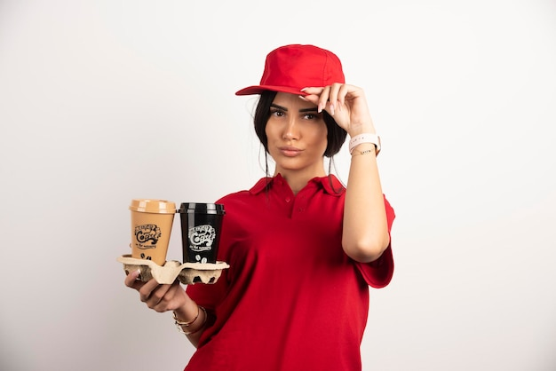 Lieferfrau mit kaffee, der ihre kappe hält. hochwertiges foto