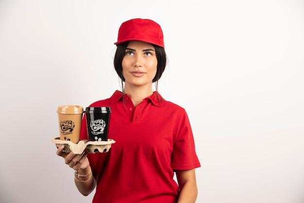 Lieferfrau mit kaffeetassen, die auf weißem hintergrund aufwerfen. hochwertiges foto