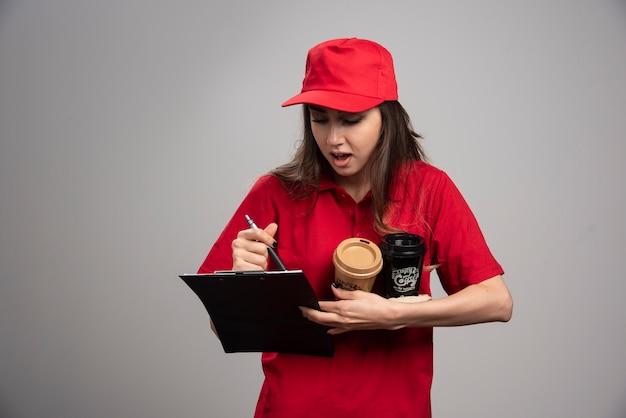 Lieferfrau mit kaffeetassen, die bestellungen in die zwischenablage schreiben.