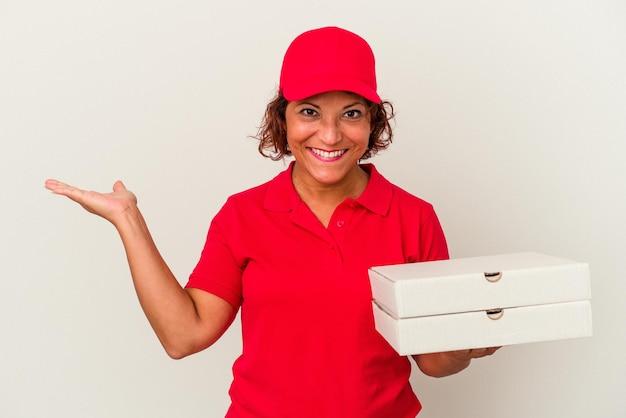 Lieferfrau mittleren alters, die pizzas einzeln auf weißem hintergrund nimmt, der einen kopienraum auf einer handfläche zeigt und eine andere hand auf taille hält.