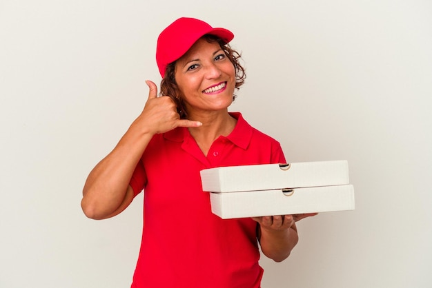 Lieferfrau mittleren alters, die pizzas einzeln auf weißem hintergrund nimmt, die eine handyanrufgeste mit den fingern zeigen.