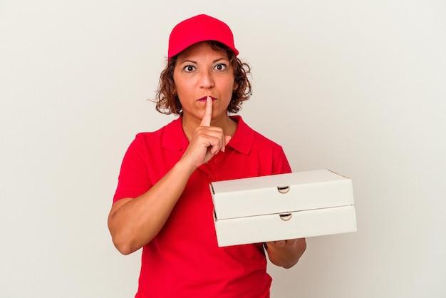 Lieferfrau mittleren alters, die pizzas einzeln auf weißem hintergrund nimmt, ein geheimnis hält oder um stille bittet.