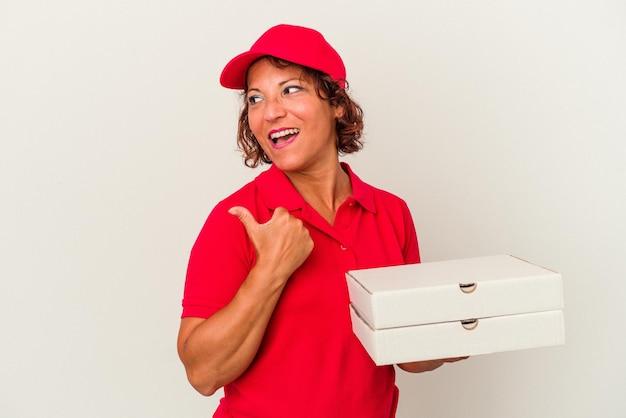 Lieferfrau mittleren alters, die pizzas einzeln auf weißem hintergrund nimmt, zeigt mit dem daumenfinger weg, lacht und sorglos.