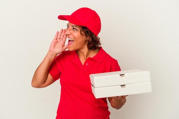 Lieferfrau mittleren alters, die pizzas einzeln auf weißem hintergrund schreit und palm nahe geöffnetem mund hält.