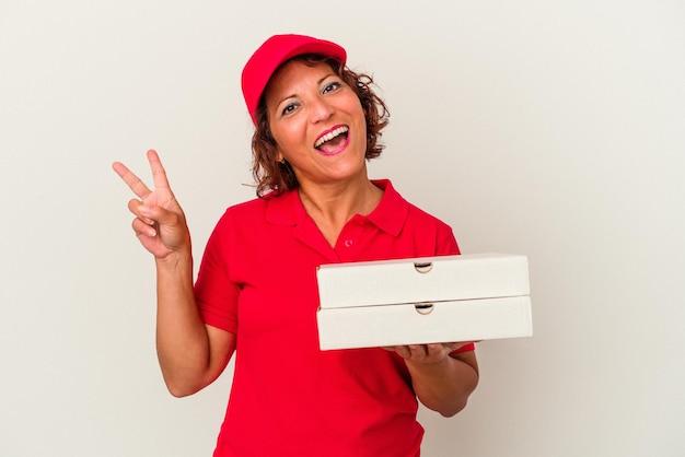 Lieferfrau mittleren alters, die pizzen einzeln auf weißem hintergrund nimmt, freudig und sorglos, die ein friedenssymbol mit den fingern zeigen.