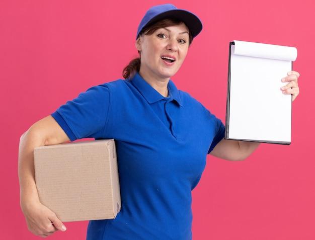 Lieferfrau mittleren alters in blauer uniform und kappe, die karton hält, zeigt zwischenablage mit leeren seiten, die vorne glücklich und positiv stehen über rosa wand schauen