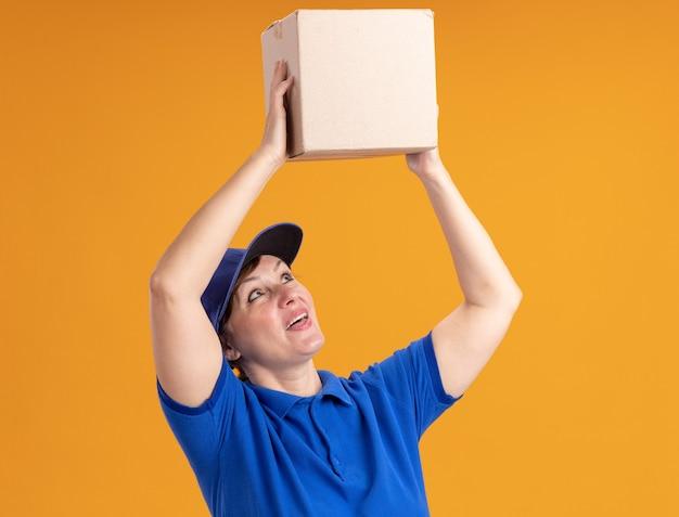 Lieferfrau mittleren alters in blauer uniform und kappe, die pappkarton über ihrem kopf hält und es mit lächeln auf gesicht betrachtet, das über orange wand steht