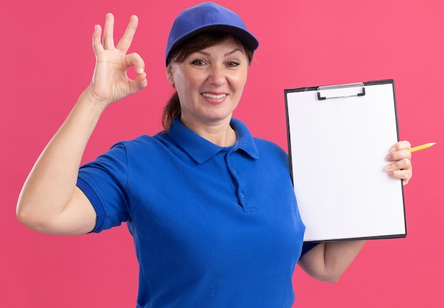 Lieferfrau mittleren alters in blauer uniform und kappe, die zwischenablage mit leeren seiten hält, die vorne lächelnd fröhlich zeigen ok zeichen, das über rosa wand steht