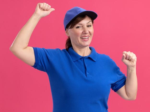 Lieferfrau mittleren alters in blauer uniform und mütze, die die fäuste glücklich und aufgeregt anhebt und sich über ihren erfolg freut, der über rosa wand steht