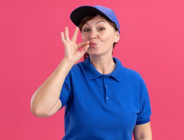 Lieferfrau mittleren alters in blauer uniform und mütze, die stille geste wie das schließen des mundes mit einem reißverschluss macht, der über rosa wand steht