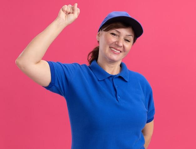 Lieferfrau mittleren alters in der blauen uniform und in der kappe, die vorne lächelnd fröhlich zeigefinger über rosa wand stehend zeigt