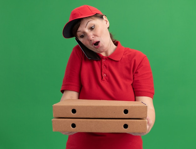 Lieferfrau mittleren alters in der roten uniform und in der kappe, die pizzakästen hält, die verwirrtes sprechen auf handy über grüner wand stehen