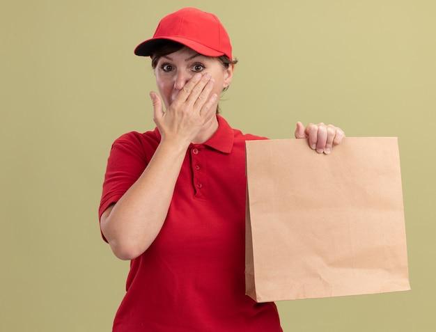 Lieferfrau mittleren alters in roter uniform und kappe, die papierpaket gibt, das vorne betrachtet wird, schockiert, mund mit hand über grüner wand bedeckend