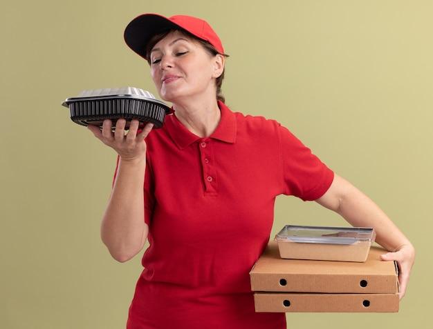 Lieferfrau mittleren alters in roter uniform und kappe, die pizzaschachteln und lebensmittelverpackungen glücklich und positiv einatmet angenehmes aroma hält, das über grüner wand steht