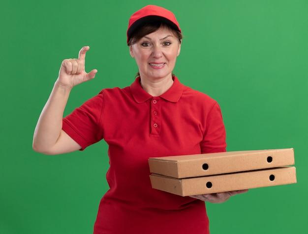 Lieferfrau mittleren alters in roter uniform und mütze, die pizzaschachteln hält, die kleine sze geste mit den fingern betrachten, die vorne lächelnd fröhlich über grüner wand stehend schauen