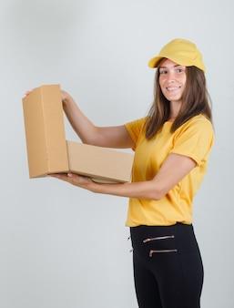 Lieferfrau öffnet pappkarton in gelbem t-shirt, hose, mütze und sieht froh aus