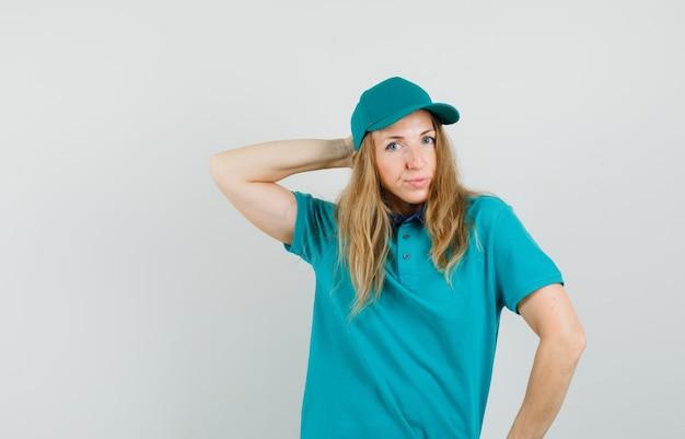 Lieferfrau posiert beim halten der hand hinter dem kopf im t-shirt, in der mütze und schaut elegant