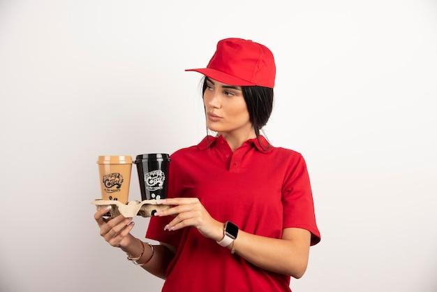 Lieferfrau posiert mit zwei tassen kaffee. hochwertiges foto