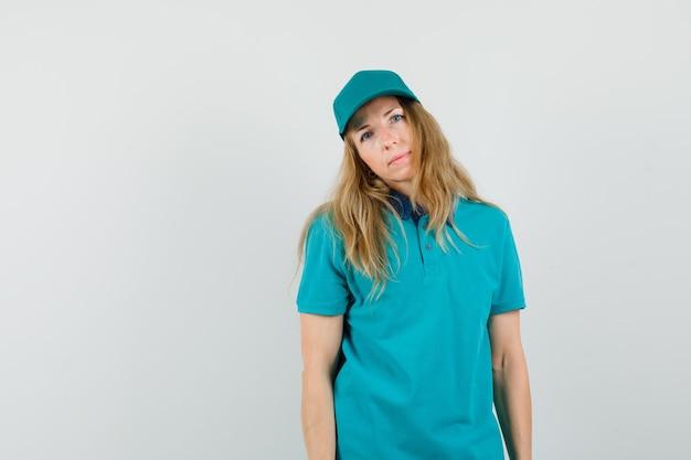 Lieferfrau verbeugt kopf auf schulter im t-shirt, mütze