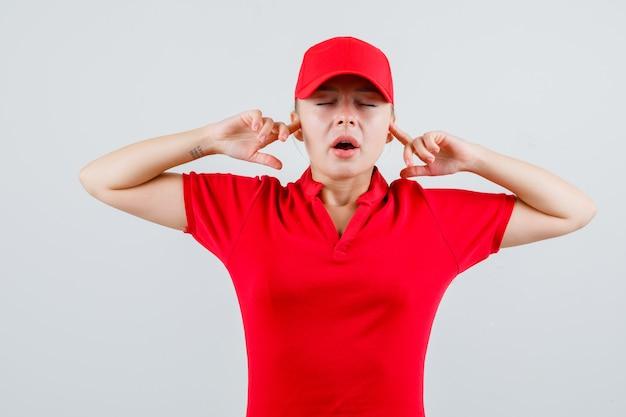 Lieferfrau verstopft ohren mit fingern in rotem t-shirt und mütze und sieht genervt aus