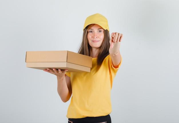 Lieferfrau zeigt finger auf kamera mit box in gelbem t-shirt, hose und mütze