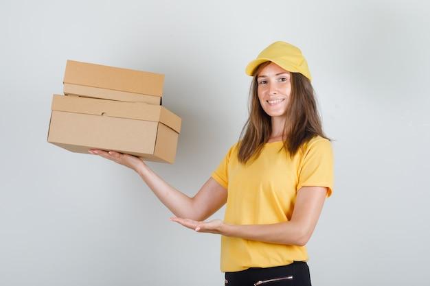 Lieferfrau zeigt pappkartons in gelbem t-shirt, hose, mütze und sieht froh aus.