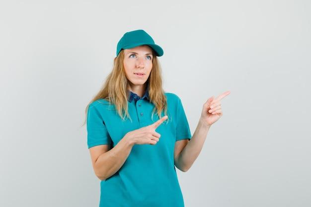 Lieferfrau zeigt weg in t-shirt, mütze und sieht nachdenklich aus