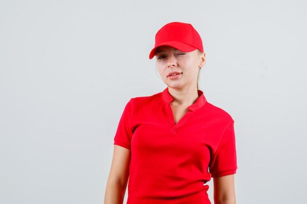 Lieferfrau zwinkert auge in rotem t-shirt und mütze und schaut selbstbewusst
