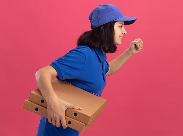Liefermädchen in blauer uniform und mützenrausch, der für die lieferung von pizzaschachteln für kunden über rosa wand läuft