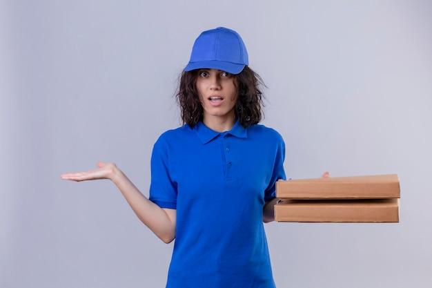 Liefermädchen in der blauen uniform, die pizzaschachteln hält, die unsicher und verwirrt aussehen und keine antwort haben, die auf weiß stehende palmen ausbreitet