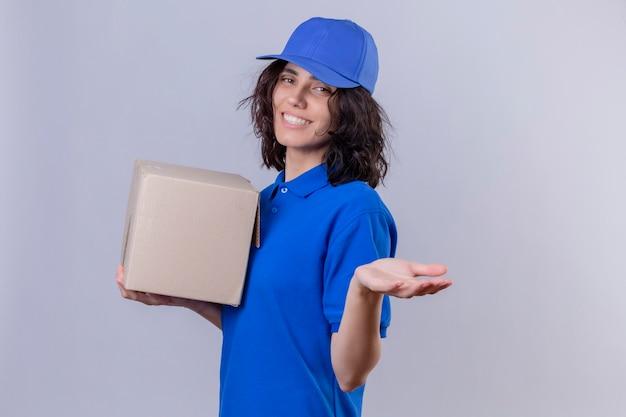 Liefermädchen in der blauen uniform und in der kappe, die boxpaket hält, das willkommensgeste mit dem lächelnden freundlichen stehen der hand macht