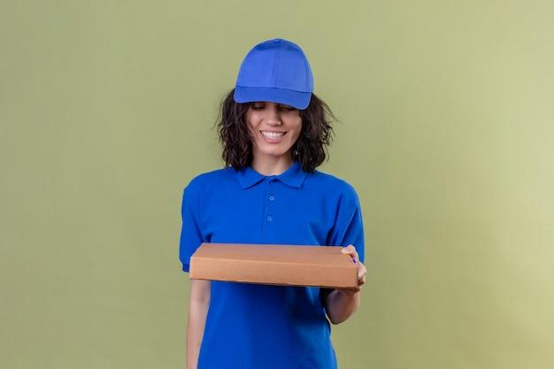 Liefermädchen in der blauen uniform und in der kappe, die die pizzaschachtel lächelnd fröhlich betrachtet, die auf stehender olivgrüner farbe steht