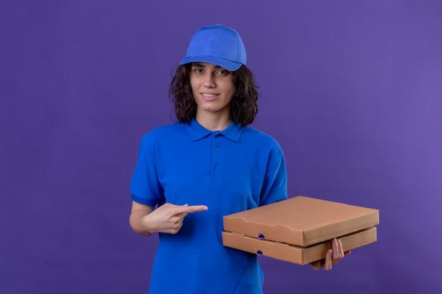 Liefermädchen in der blauen uniform und in der kappe, die mit pizzaschachteln stehen, die mit zeigefinger zu ihnen zeigen, die zuversichtlich auf lokalisiertem purpur lächeln