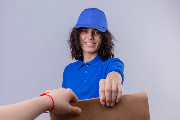 Liefermädchen in der blauen uniform und in der kappe, die papierpapier zu einem kunden geben, der freundlich über isolierten weißen raum lächelt