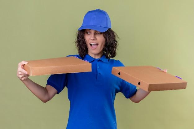 Liefermädchen in der blauen uniform und in der kappe, die pizzaschachteln halten, die aufgeregt und überrascht über isoliertem olivgrünen farbraum stehen