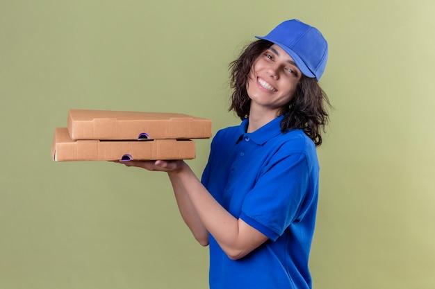 Liefermädchen in der blauen uniform und in der kappe, die pizzaschachteln halten, die freudig positiv und glücklich lächelnd fröhlich stehend auf lokalisiertem grün suchen