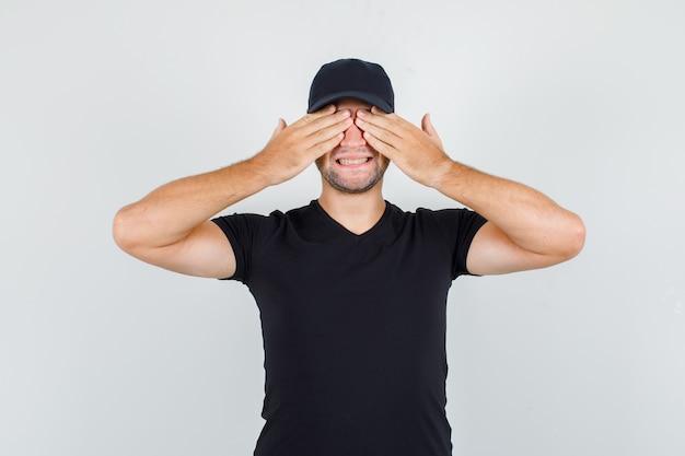 Liefermann, der hände auf augen im schwarzen t-shirt hält