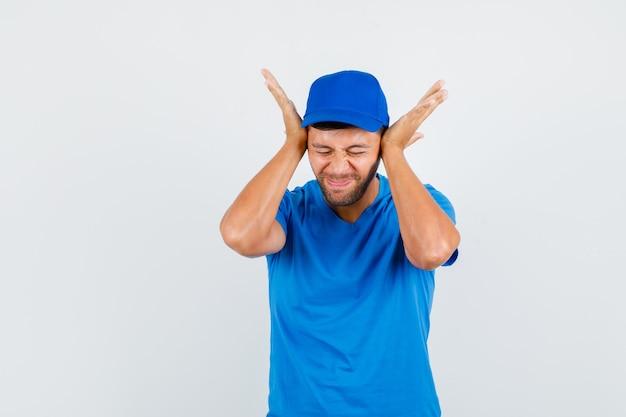 Liefermann, der hände auf den ohren im blauen t-shirt hält