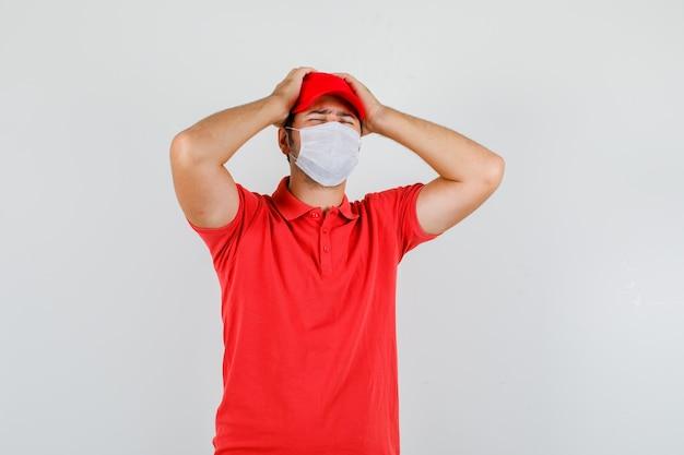 Liefermann, der hände auf kopf im roten t-shirt hält