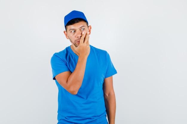 Liefermann, der hand auf gesicht im blauen t-shirt hält