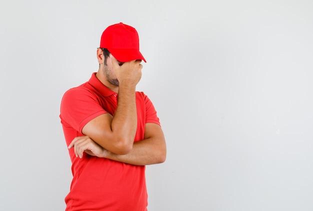 Liefermann, der hand auf gesicht im roten t-shirt hält