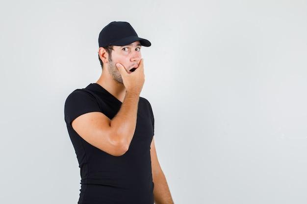 Liefermann, der hand auf mund im schwarzen t-shirt hält