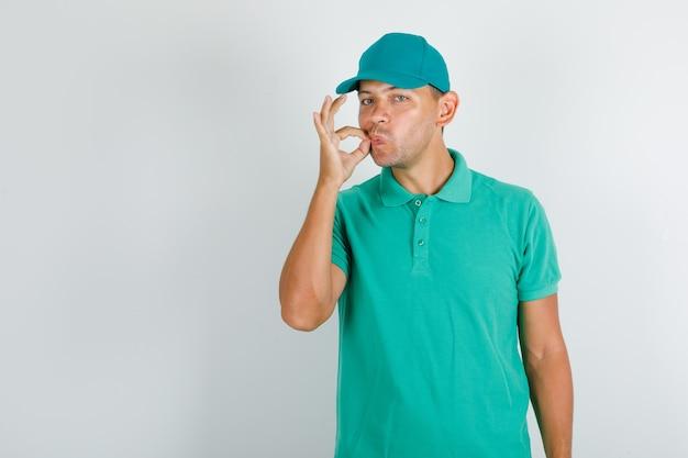 Liefermann, der köstliche geste im grünen t-shirt mit kappe macht