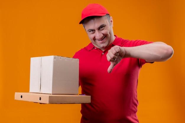 Liefermann, der rote uniform und kappe hält, die pappkarton und pizzaschachteln lächelnd zeigt, zeigt daumen nach unten und schaut schlau auf kamera stehend
